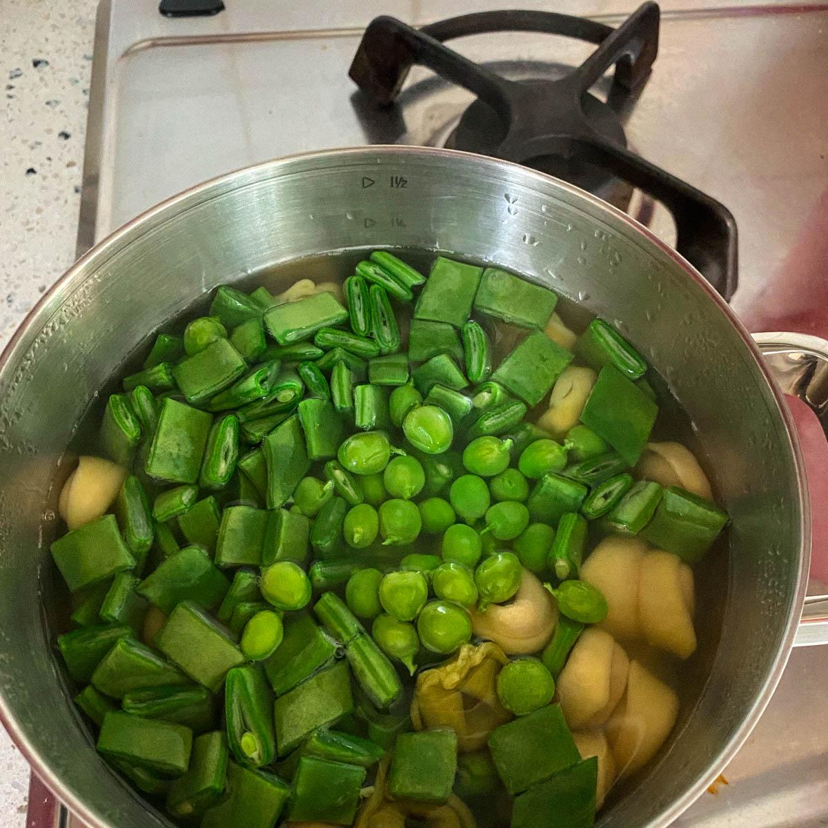 Kook de snijboon en erwten mee met de tortellini