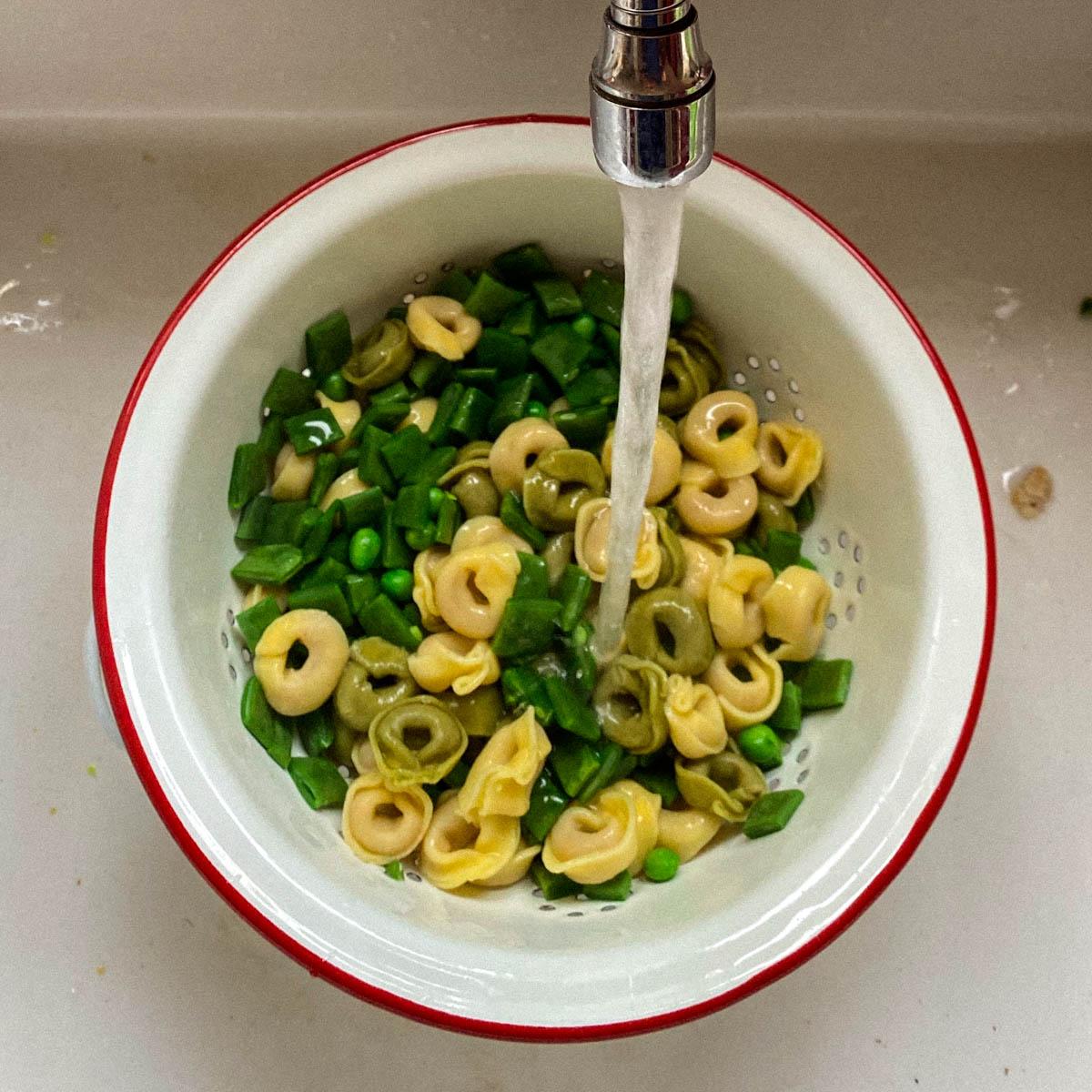 Koel de tortellini en groentes onder koud water af
