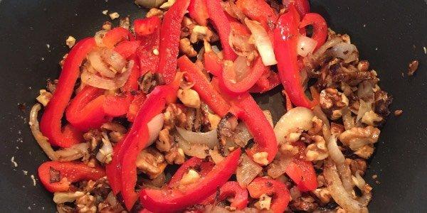 De uien, walnoten en paprika in de hapjespan